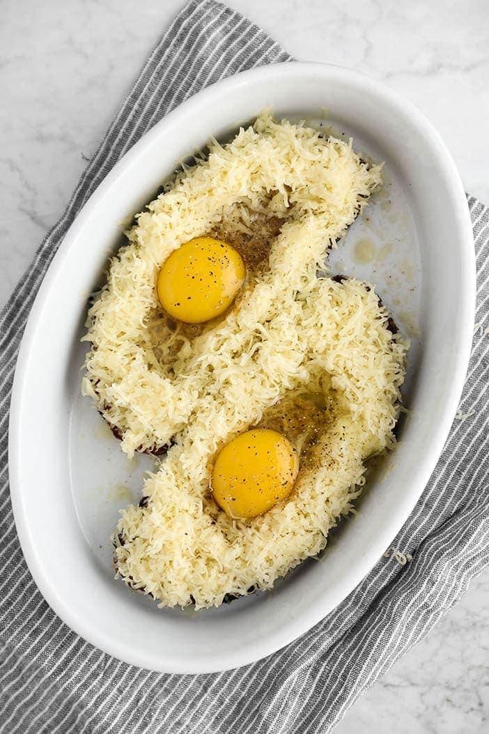 Eggs nesting on toasts with grated cheese, ready to be baked