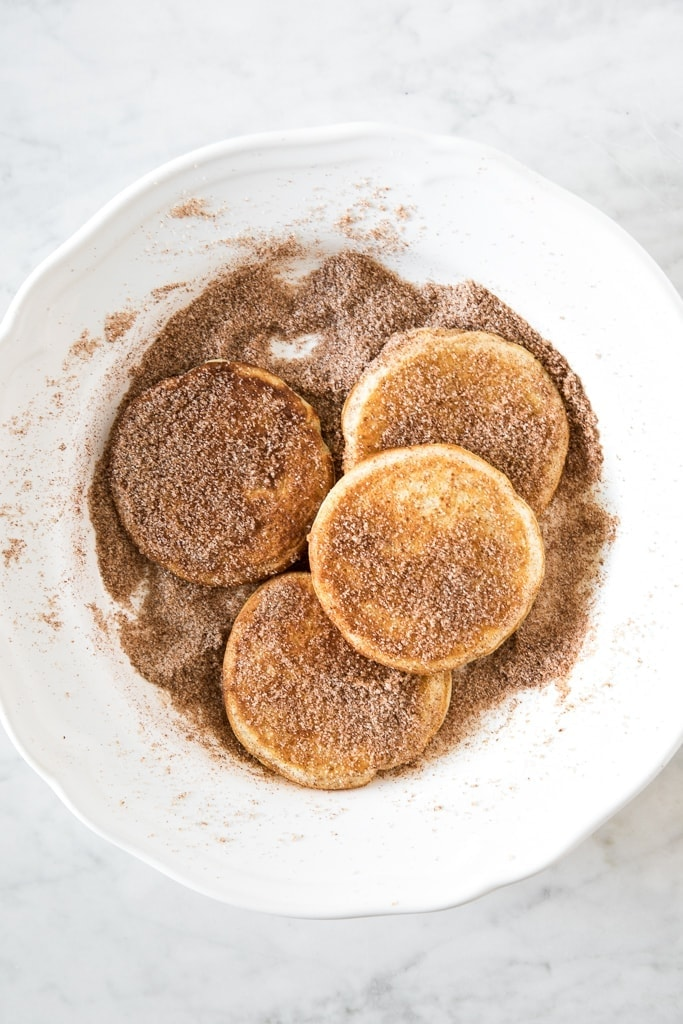 Plate of pancakes topped with sugar and cinnamon