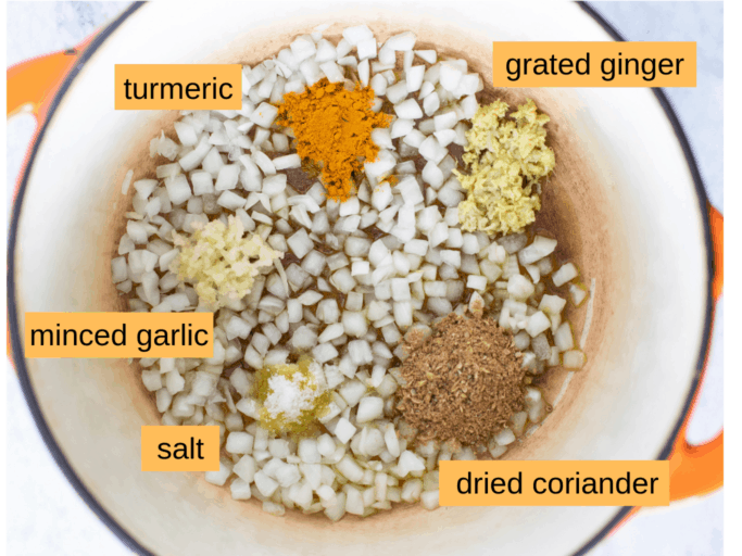 chickpea curry aromatics ingredients: turmeric, grated ginger, dried coriander, salt, minced garlic, and onion in a large pot with olive oil