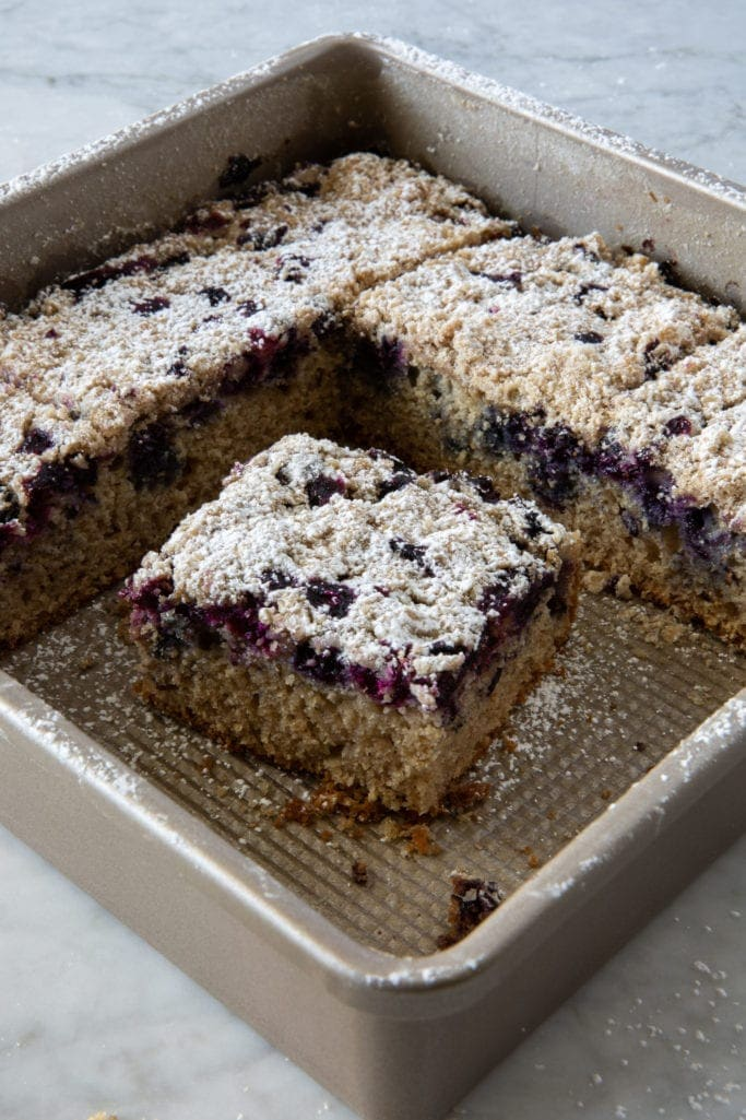 Slice of blueberry crumb cake inside of a square baking pan