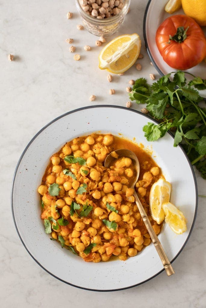 Plate with chickpea tomato curry with lemon wedge and spoon