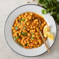 Plate of chickpea tomato curry, with lemon wedges and spoon