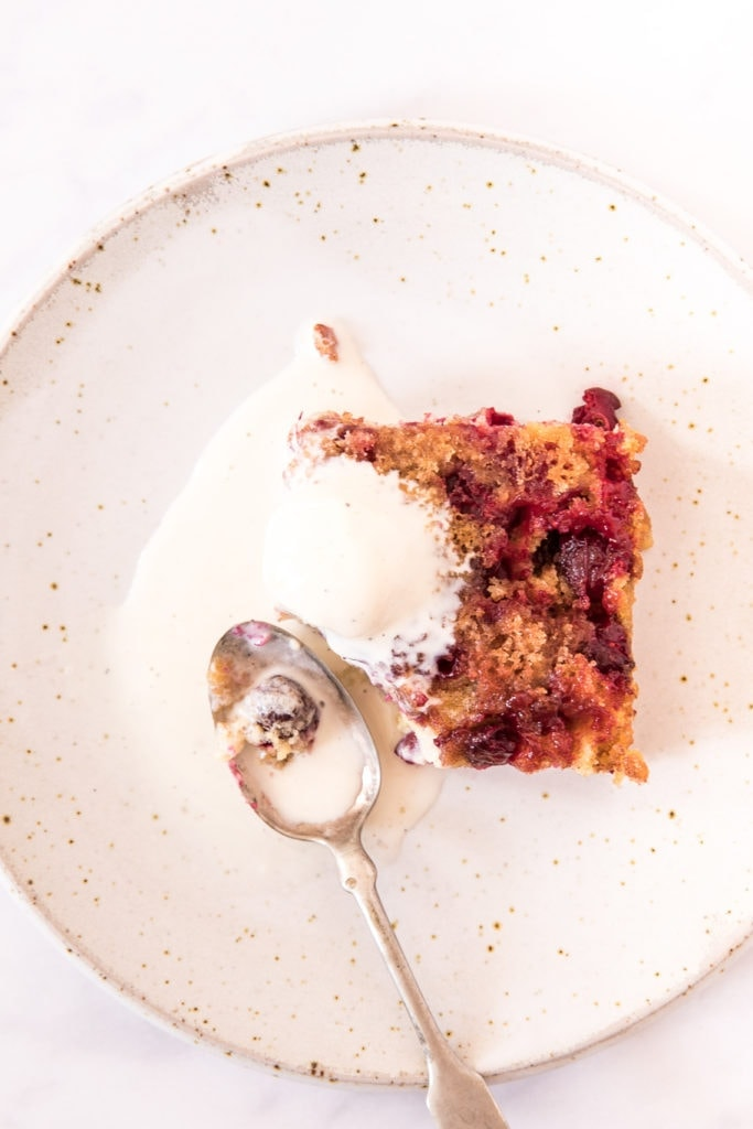 vie of a slice of cranberry upside down cake from above. served with vanilla ice cream. spoon