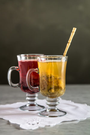 two glasses with roasted fruit tea. red glass mug with berry tea and yelllow/green with tropical variation