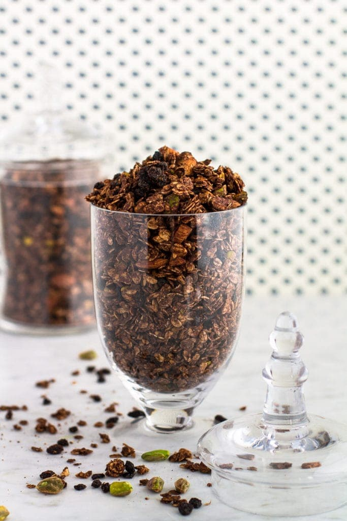 two glass containers with Chocolate Granola With Pistachios, Almomonds and Dried currants