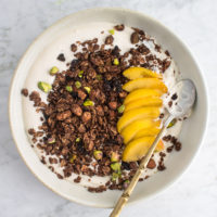 bowl of yogurt with chocolate granola and sliced peaches