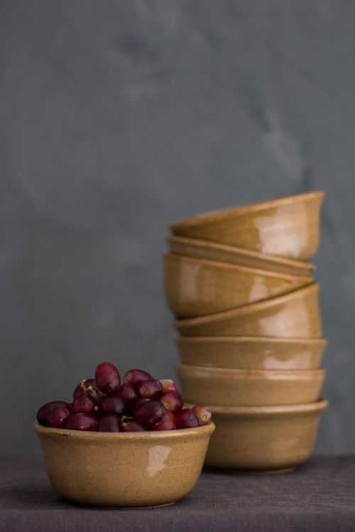 ceramic brown bowl with grapes in the forefront and a stockpile of same bowls in the background
