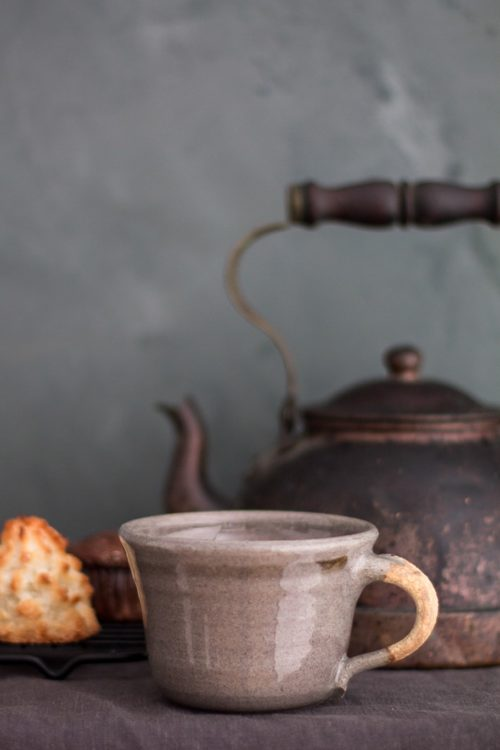 grey ceramic tea cup with teapot in the background and a macaroon on the side
