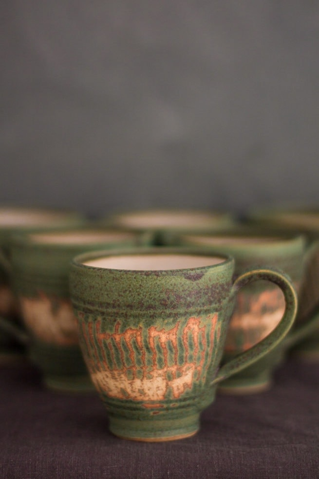 green ceramic tea cup with abstract design