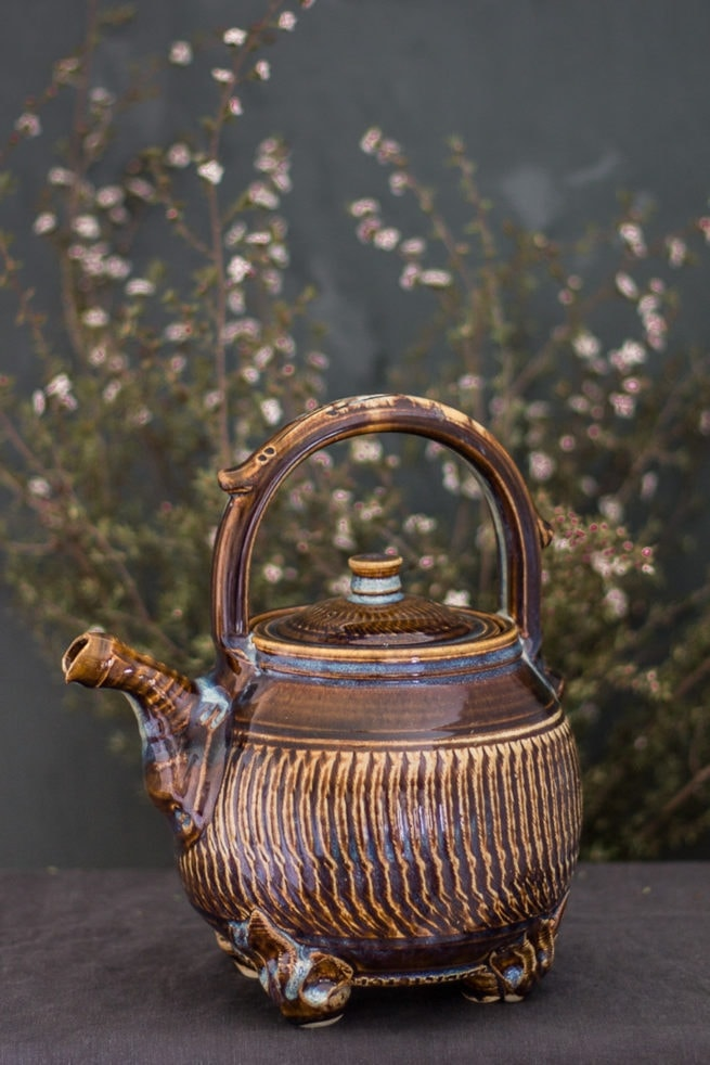 round multi colored ceramic teapot with flowers in the background