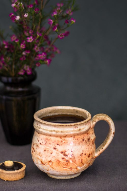 orange textured cup with cookie in the foreground and vase with flowers in the background
