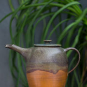 Ceramic teapot with waves design, orange, brown, red colors with a green plant in the background