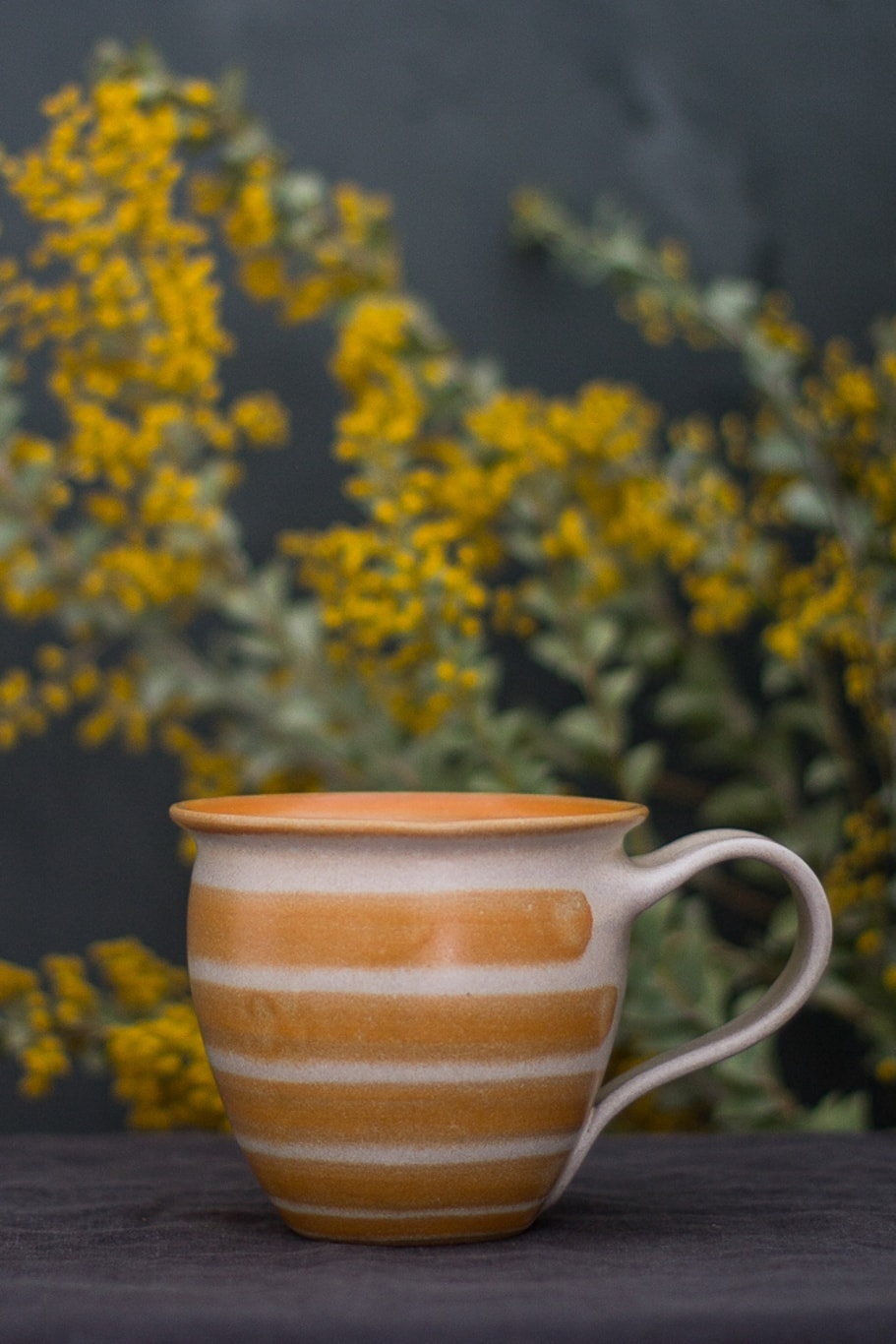orange stripe ceramic cup with yellow flowers in the background