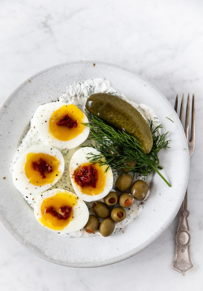 plate with tzatziki, soft boiled eggs with harissa, pickle, dill, and olives