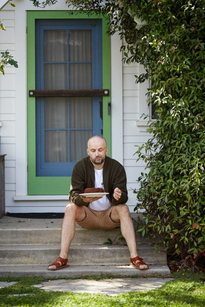 michal martinek sitting on a porch, holding a cake on a plate