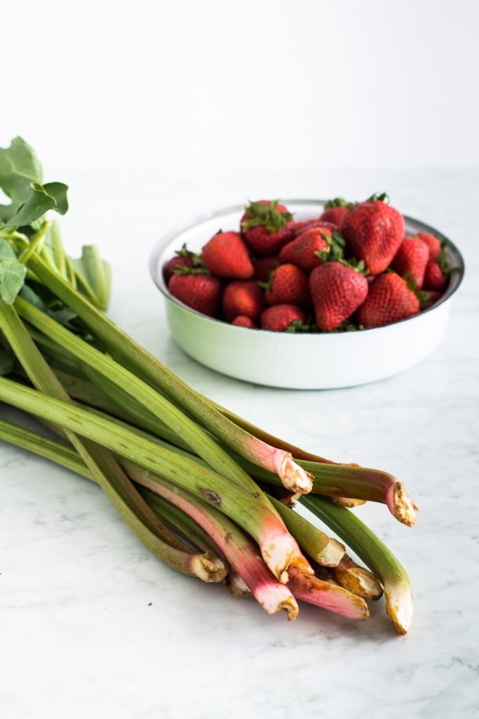 rhubarb sticks with a bowl of strawberries