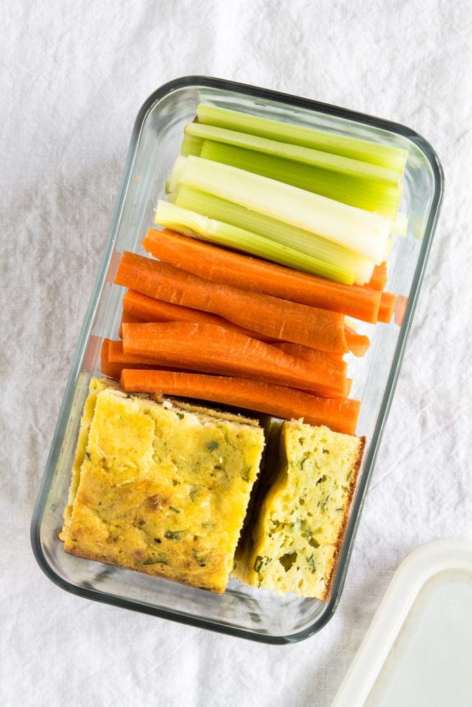 zucchini feta slices in a glass container with celery and carrot sticks