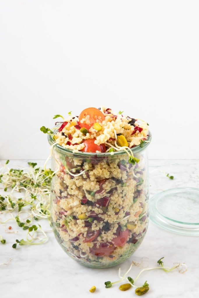 Glass jar with quinoa salad with tomatoes, pistachios, radicchio, daikon sprouts