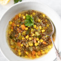 Bowl of red quinoa soup with corn, zucchini, carrots,