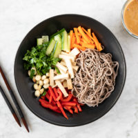 black bowl with soba noodle salad, with peanut butter dressing on the side