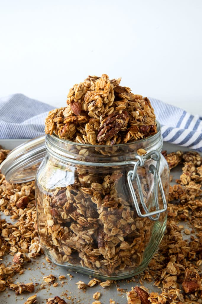 Glass jar with big-cluster granola. Made with oats, pecans, almonds, honey and flaxseed