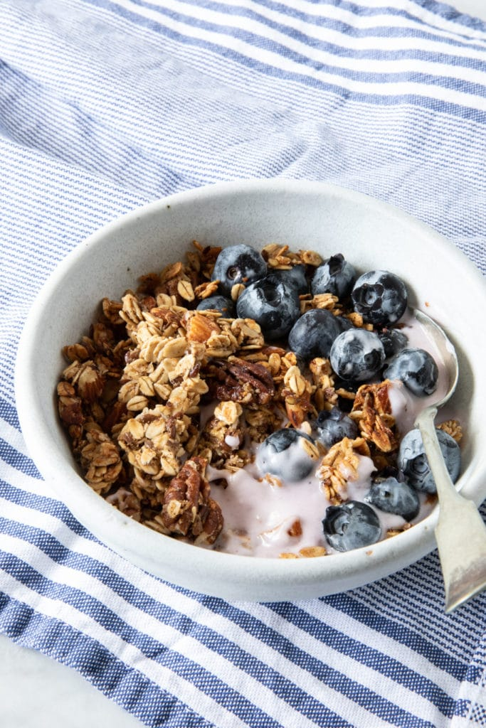 Bowl with big-cluster granola. Made with oats, pecans, almonds, honey and flaxseed. Served with yogurt and blueberries.