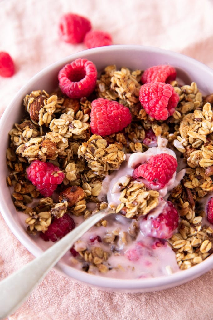 Bowl with big-cluster granola. Made with oats, pecans, almonds, honey and flaxseed. Served with yogurt and raspberries.