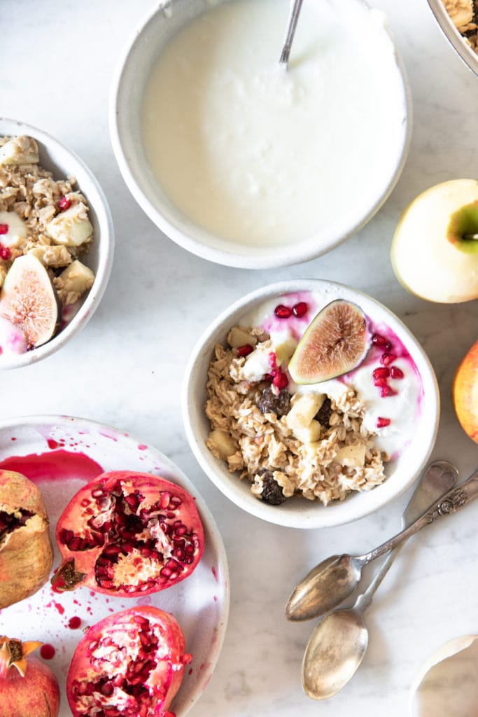 Bowls with Bircher Muesli (overnight oats), peeled apple, spoons, fresh figs, pomegranate seeds, and yogurt