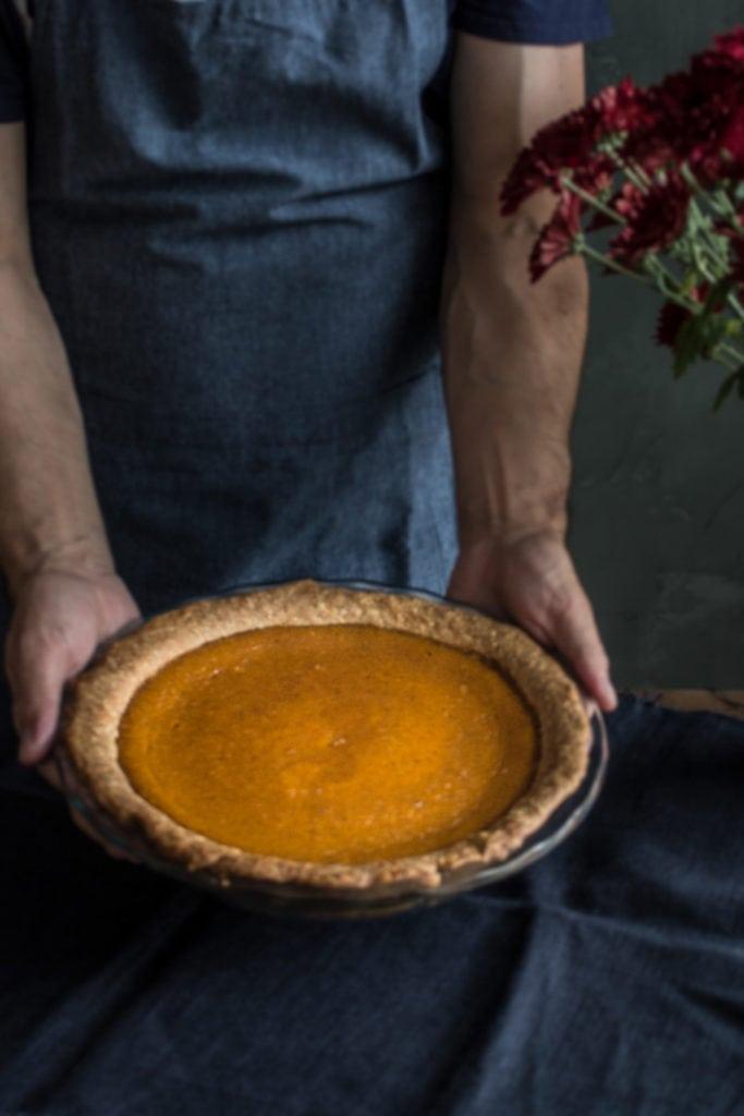 Holding a pumpkin pie with spelt crust