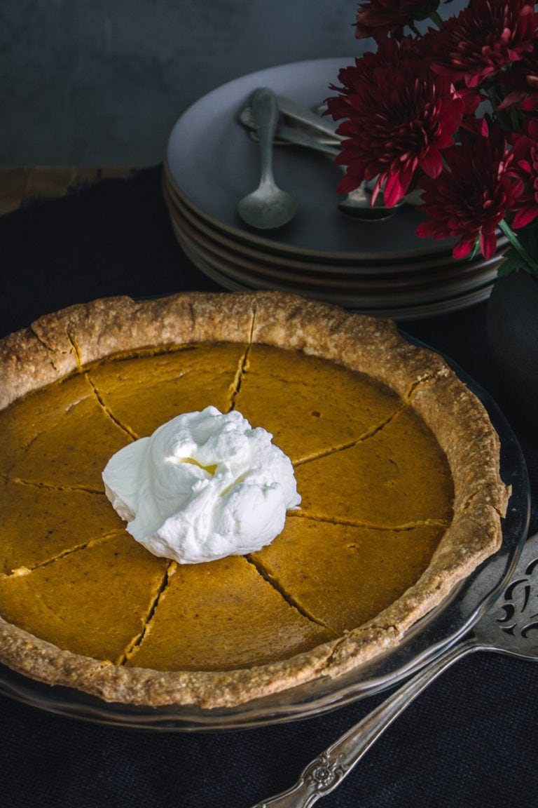 Sliced pumpkin pie with spelt crust, topped with whipped cream
