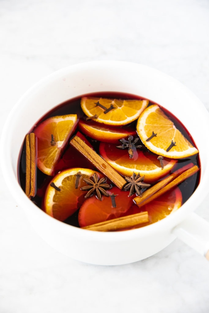 White saucepan with ingredients for mulled wine: red wine, cinnamon sticks, sliced orange, star anise and whole cloves