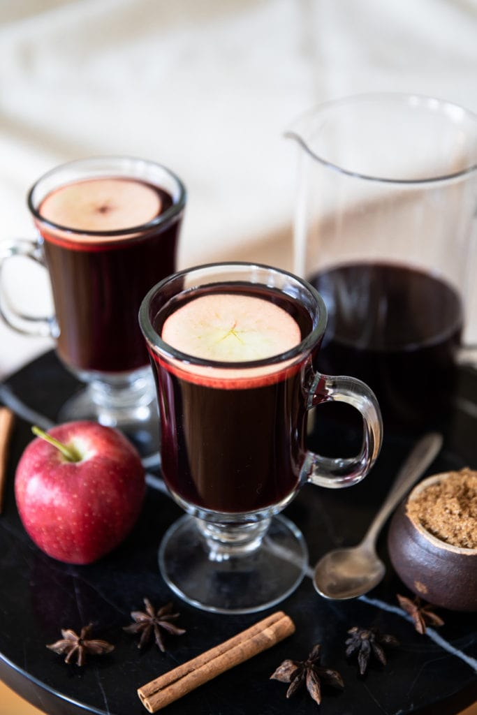 Glass mugs with red mulled wine, arranged on a coffee table with red apple, cinnamon sticks, star anise, brown sugar, and teaspoon