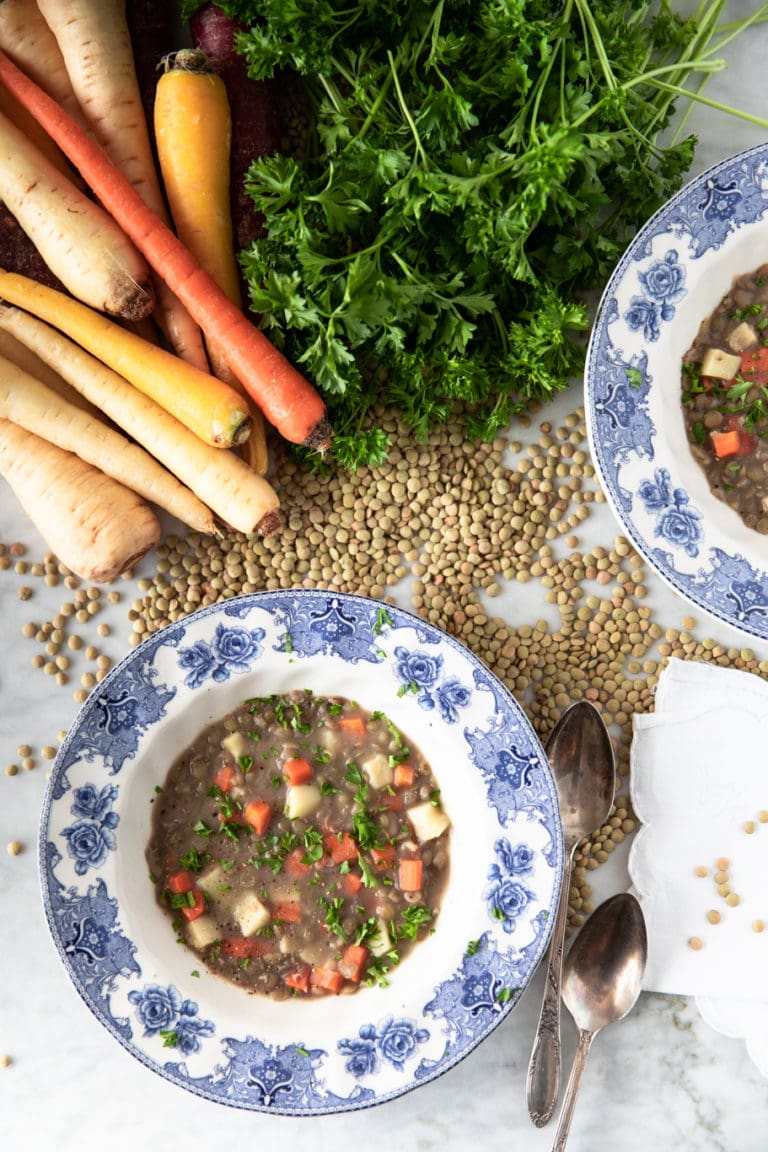 White soup plate with blue flowers with green lentil soup with carrots and parsnips
