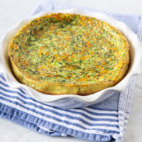 Crustless carrot zucchini quiche in a baking dish, on top of a blue/white kitchen towel