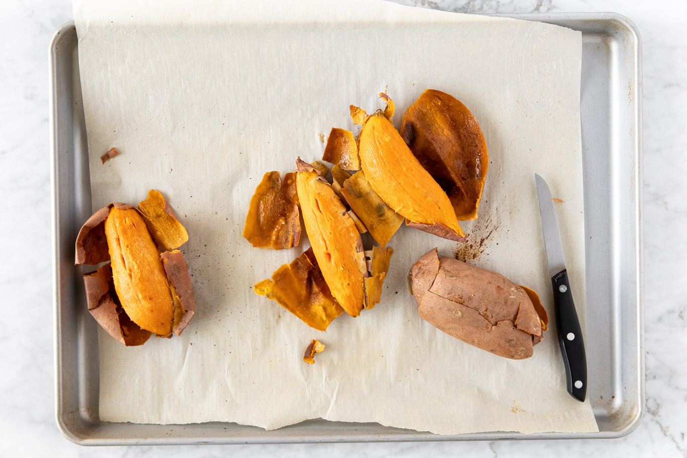 Baking sheet with peeled, roasted sweet potatoes