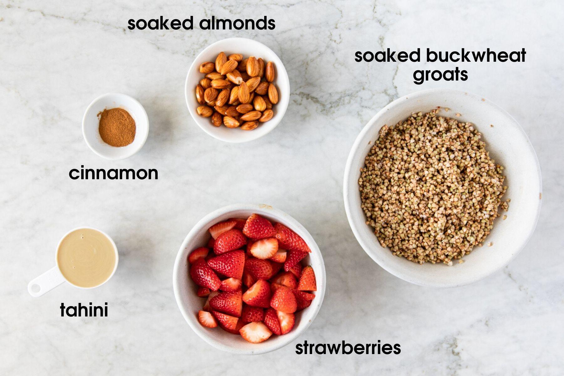 bowls with ingredients to make vegan raw buckwheat groats porridge including cinnamon, soaked almonds, soaked buckwheat groats, strawberries and tahini