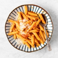 Plate with Easy Creamy Penne Alla Vodka Recipe, with a spoon, and grated parmesan cheese