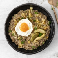 Plate with sweet sour green lentils stew, topped with fried onion, sunny side up egg, pickles and freshly chopped parsley