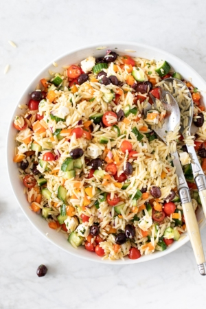 Bowl and serving utensils with 15-Minute Orzo Pasta Salad