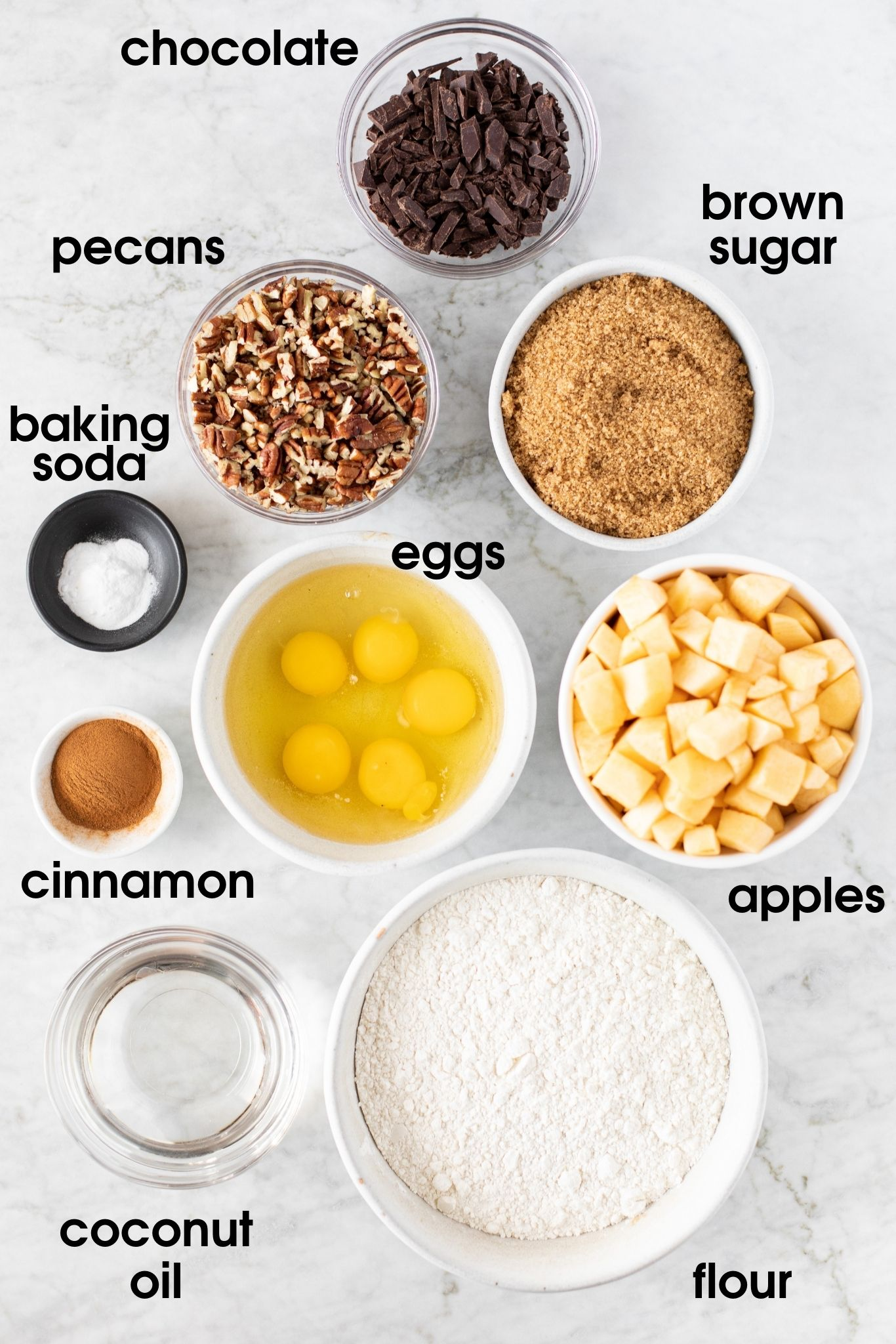 Overview of ingredients for Apple Pecan Chocolate Coffee Cake including chocolate, brown sugar, apples, flour, coconut oil, cinnamon, eggs, baking soda, and pecans | from verygoodcook.com