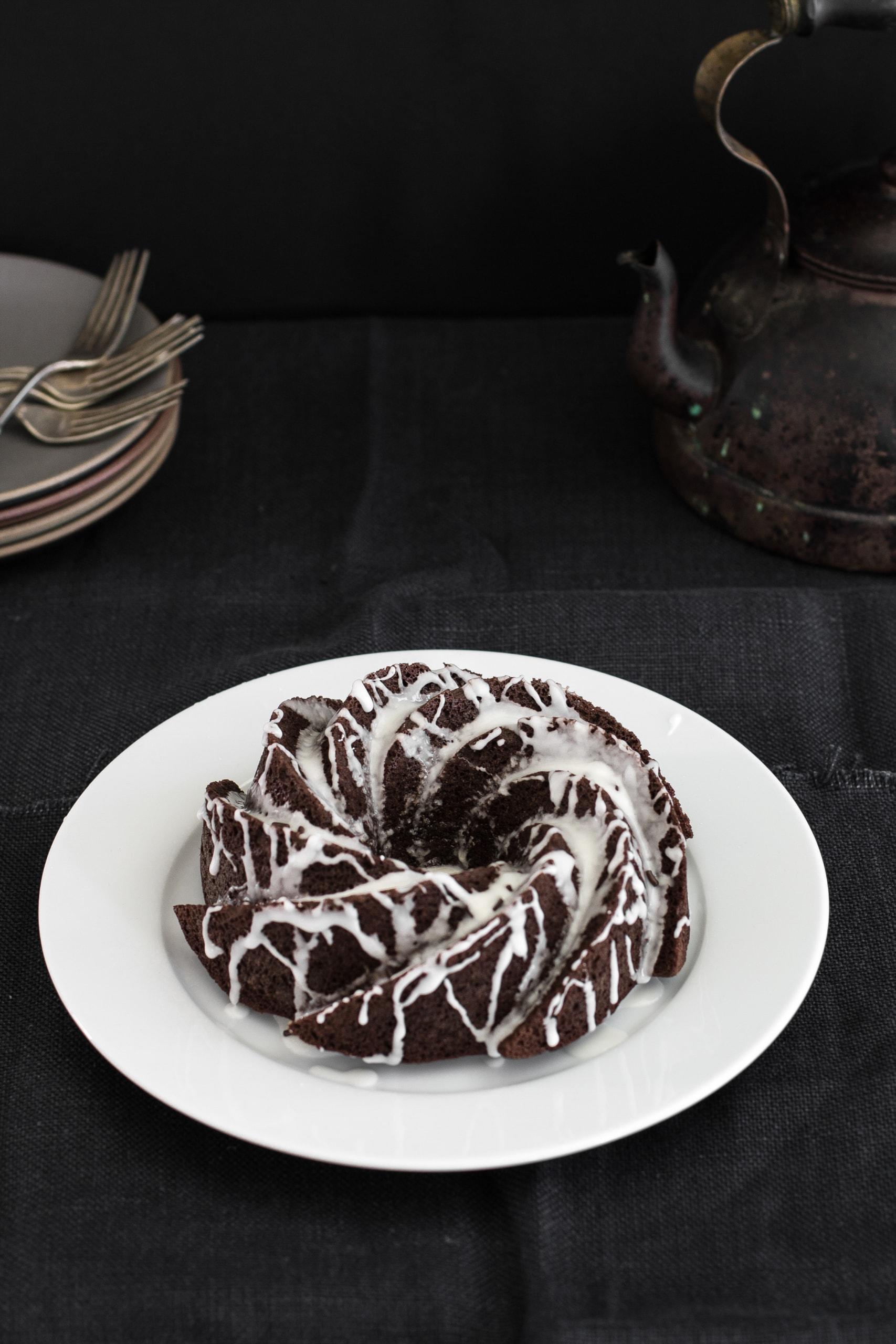 Chocolate Banana Paleo Cake on a plate, drizzled with lemon glaze- from verygoodcook.com